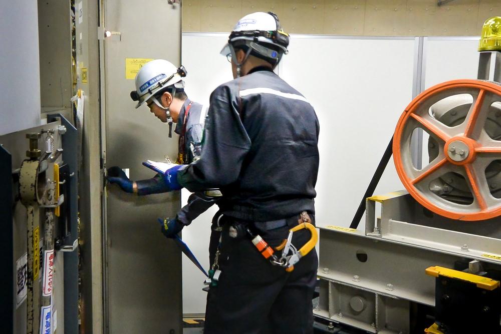 法定検査作業競技中の梅村氏(写真奥)。研修施設内に設置された旧方式のエレベーター実機にて、 制御盤を開き絶縁抵抗を測定中(撮影時:2017年)